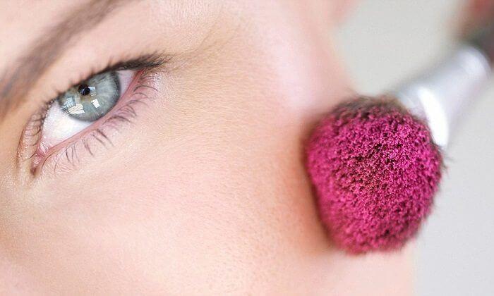 B18KJY woman applying pink blush on cheek